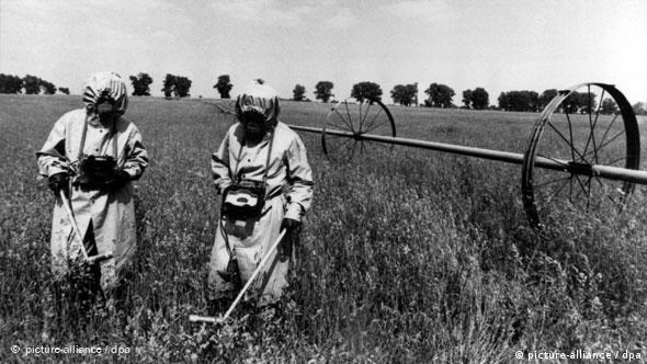 Soviet nuclear worker test radiation levels in a field surrounding Chernobyl