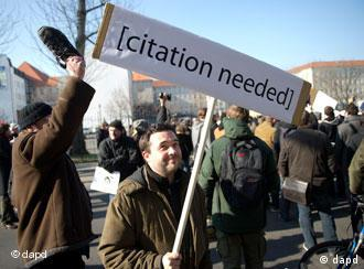 A protester holds a sign that reads 'citation needed'
