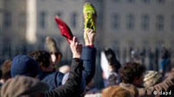 Protesters in Berlin hold up their shoes