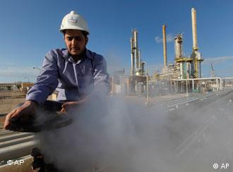 A Libyan oil worker, works at a refinery inside the Brega oil complex, in Brega east of Libya, on Saturday Feb. 26, 2011. Production at Brega has dropped by almost 90 percent amid the country's crisis because many employees have fled and few ships are coming to offload the product. (AP Photo/Hussein Malla)
