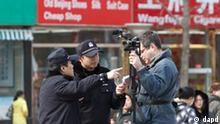 Chinese policemen ask an Associated Press cameraman to leave the area near the shopping street of Wangfujing in Beijing Sunday, Feb. 27, 2011. Large numbers of police and the use of new tactics like shrill whistles and street cleaners are squelching any overt protests in China after calls for more peaceful gatherings modeled on recent democratic movements in the Middle East. (AP Photo/Andy Wong)