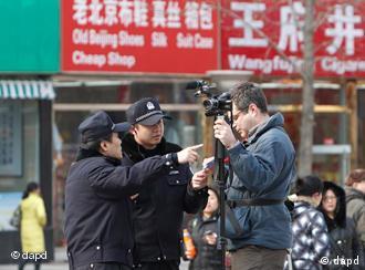 Chinesische Polizisten kontrollieren einen ausländischen Kameramann in der Pekinger Wangfujing-Straße (Foto: AP)