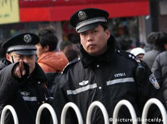 epa02604601 A policeman guarding the entrance to Wangfujing street points to a photographer in central Beijing, China, on 27 February 2011. Police barred foreign reporters from the site of a planned anti-government protest in Beijing 27 February amid the tightest security in the Chinese capital since the 2008 Olympic Games. Scores of uniformed and plain-clothes police moved people away from the area around a fast food restaurant in the nearby Wangfujing shopping street where activists called for weekly protests each Sunday afternoon. EPA/HOW HWEE YOUNG  +++(c) dpa - Bildfunk+++  ### usage Germany only, Verwendung nur in Deutschland ###