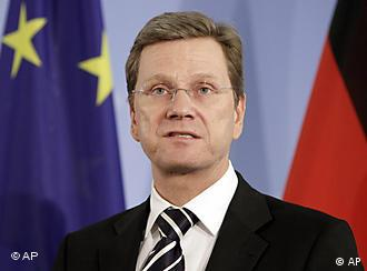 German Foreign Minister Guido Westerwelle in front of German and EU flags