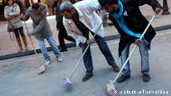 Tunisian students sweep a street in Tunis