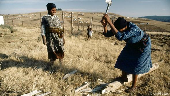 A woman in South Africa chops wood
