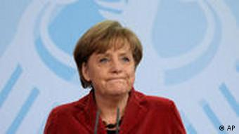 Wearing a red blazer, Angela Merkel looks off camera despondently. (Photo: Clemens Bilan/dapd)