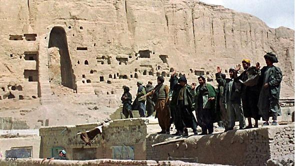 Taliban soldiers stand in front of empty shell where a Buddha statue stood, while waving to journalists, Monday, March 26, 2001 in Bamiyan, Afghanistan. Ignoring worldwide criticism by Muslims, Buddhists and art lovers, Taliban officials showed off their destruction of two ancient statues on Monday by taking foreigners to the Bamiyan mountainside where the relics were blasted apart. (AP Photo/Amir Shah)