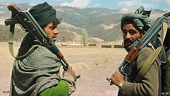 Taliban soldiers with guns stand guard in Bamiyan