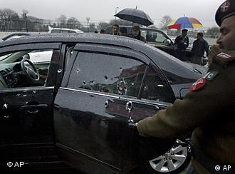 A soldier examines the damaged car of the slain Pakistani minorities minister