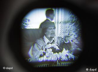 Libyan Leader Moammar Gadhafi is seen through a television camera viewfinder as he speaks in Tripoli, Libya, Wednesday, March 2, 2011. Gadhafi spoke to supporters and the media at an event to celebrate the 34th anniversary of the declaration of transferring the Power to the masses, and announcing the establishment of the Republic of the Masses. (AP Photo/Ben Curtis)