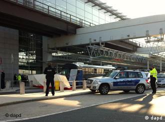 A police vehicle and a covered bus outside terminal 2 of Frankfurt airport, police officers are securing the scene