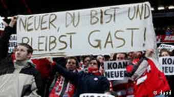 Bayern fans at their home ground with a sign reading Neuer, you are and remain a guest