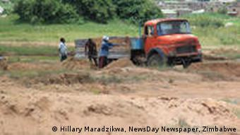 Illegal sand miners load a truck for building contractors rural Zimbabwe