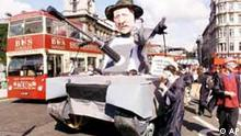 Peace activists bring a model of a tank, with an effigy of U.S. President George W. Bush as a turret into Parliament Square, London, blocking the traffic, Thursday Sept. 26, 2002.