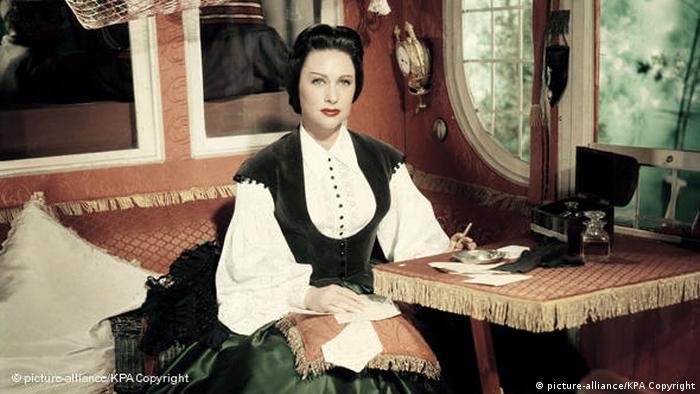 Szene aus dem Film Lola Montez von 1955 mit Martine Carol in Kutsch am Tisch mit Zigarette (picture-alliance/KPA Copyright)