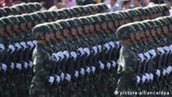 Rows of Chinese soldiers in green uniforms and white gloves