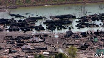 The remnants of a village sit in a muddy lake formed by oozing mud from the volcano