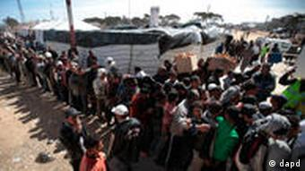 People fleeing the unrest in Libya wait to receive clothes, on the border with Tunisia