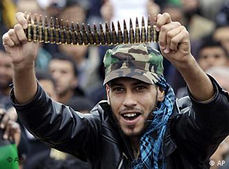 Anti-Libyan Leader Moammar Gadhafi protester, holds up bullets during a protest after Friday prayer at the court square, in Benghazi, eastern Libya, Friday March 4, 2011