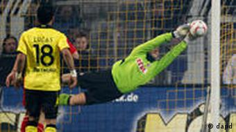 Cologne goalkeeper Michael Rensing parries a shot during the match