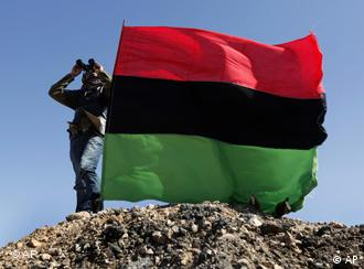 Libyan rebel looks through his binocular toward the sky, behind a waving rebel flag
