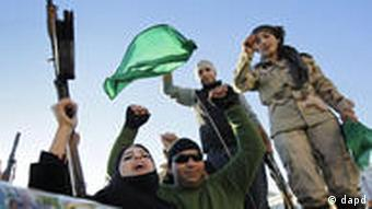 The female relative of a fighter, center, holds his gun in the air, as pro-Gadhafi soldiers and supporters gather to celebrate in Green Square, Tripoli, Libya