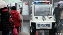 Police officers drive an electric police patrol car through a busy shopping street under the rain in Shanghai, China, Sunday, March 6, 2011. (AP Photo/Eugene Hoshiko)