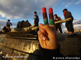 Person holdign fingers painted in Libyan colors, while children play on tank in Benghazi