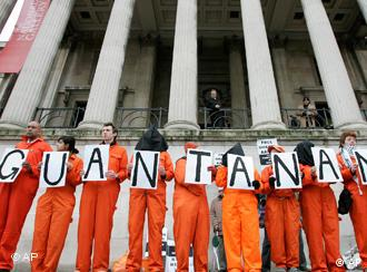 Back-dropped by columns of the National Gallery, campaigners in orange jumpsuits from the London Guantanamo Campaign hold a silent vigil in Trafalgar Square, London Tuesday, Jan. 11, 2011. Human rights groups demanded the release of the last British inmate at Guantanamo Bay on Tuesday, donning orange jumpsuits to demonstrate against the U.S. prison's ninth anniversary. (AP Photo/Akira Suemori)