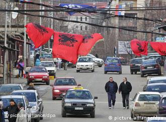 epa02620431 Pedestrians walk under Albanian flags (top front) placed in the southern Albanian-dominated part and Serbian flags (top back) in the northern Serb-dominated part of ethnically divided town of Mitrovica, Kosovo, 07 March 2011. Serbia and Kosovo will hold their first direct talks 08 March 2011 since Kosovo declared independence from Serbia in February 2008. The talks come after intense pressure from the EU, which both countries hope to join. EU diplomat Robert Cooper will mediate the two-day meeting. EPA/VALDRIN XHEMAJ