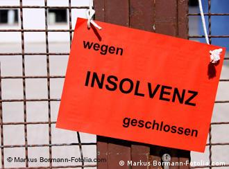An orange sign that says Closed due to bankruptcy in German