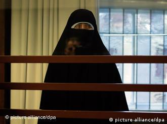 Defendant in burqa with eyes blurred out