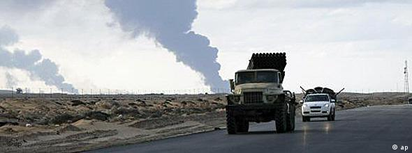 mobile rocket launcher in street with smoke in background