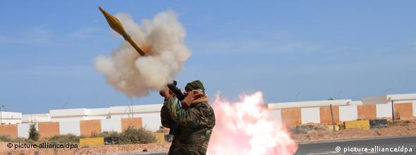 A rebel fighter fires his Rocket-Propelled Grenade launcher (RPG) at a Libyan airforce plane