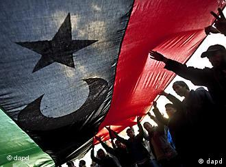 Libyans hold a large pre-Gadhafi flag