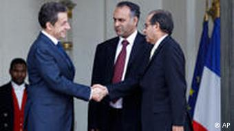 French President Nicolas Sarkozy, left, shakes hands with Mahmoud Jibril, right, and Ali Al-Esawi, representatives of the newly formed Libyan council