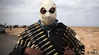 A Libyan volunteer carries ammunition on the outskirts of the eastern town of Ras Lanouf, Libya,