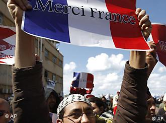 An anti-Libyan leader Moammar Gadhafi protester holds up a French flag with French words read: Thanks France, during a protest