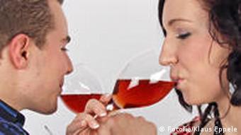 Ein Mann und eine Frau halten Gläser in den Händen und trinken Brüderschaft