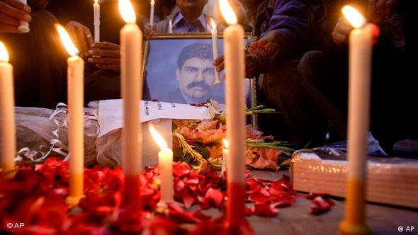 Pakistani Christians light candle next to portrait of their slain leader Shahbaz Bhatti