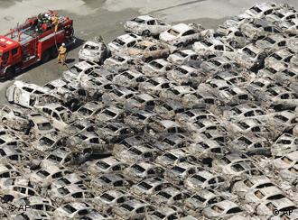 A firefighter looks at burned-out vehicles at Hitachi port