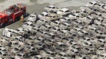 A firefighter looks at burned-out vehicles at Hitachi port, northeastern Japan