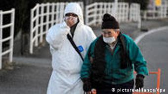 An elderly resident being taken to a shelter by a man wearing a protective outfit near the nuclear plant at Fukushima prefecture