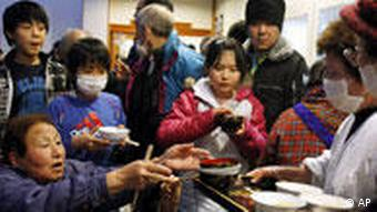 People taking a shelter by an evacuation order are provided hot meal in Namiemachi in Fukushima Prefecture (State) as Fukushima Daiichi power plant's Unit 1 affected by a massive earthquake is facing a possible meltdown, Saturday, March 12, 2011, one day after a giant quake and tsunami struck the country's northeastern coast. (AP Photo/Kyodo News) MANDATORY CREDIT, NO LICENSING ALLOWED IN CHINA, HONG KONG, JAPAN, SOUTH KOREA AND FRANCE