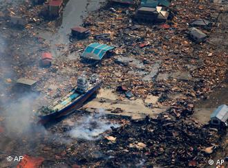 A ship washed away by tsunami sits amid debris in Kesennuma, Miyagi Prefecture, Sunday, March 13, 2011 after Japan's biggest recorded earthquake hit its eastern coast Friday. (AP Photo/Itsuo Inouye)