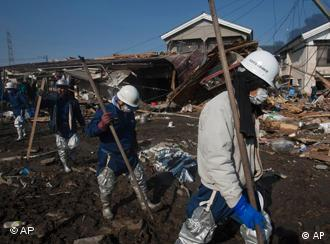 Japanese recovery teams enter a destroyed area of Sendai