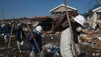 Japanese recovery teams enter a destroyed area of Sendai, northeastern Japan