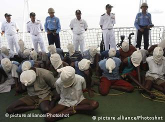 Suspected Somali pirates sit with their faces covered with cloth sacks on the deck of an Indian Coast Guard vessel