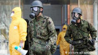 Japanese Self Defense Forces wearing anti radiation gear search for evacuees in Otama village, Fukushima prefecture, Japan, 13 March 2011.